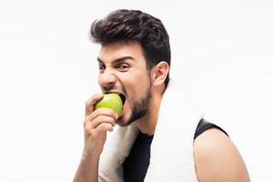 Fitness man eating apple