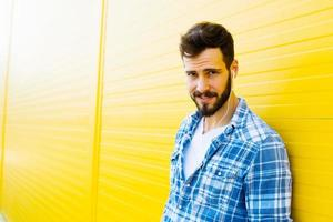 young handsome man with headphones on yellow wall photo