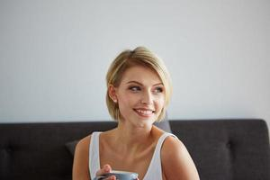 Happy smiling beautiful blond woman awaking with cup of coffee