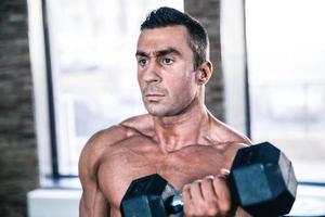 entrenamiento de hombre musculoso con mancuerna