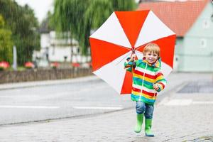 Beautiful child with red umbrella and colorful jacket outdoors a photo