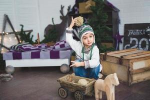 garoto bonito senta e brinca com um brinquedos de madeira