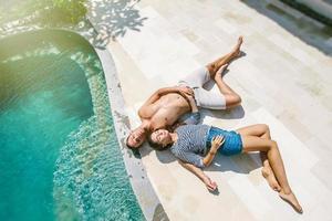Love couple lying near swimming pool on luxury villa