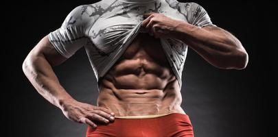 Muscular man in studio on dark background photo
