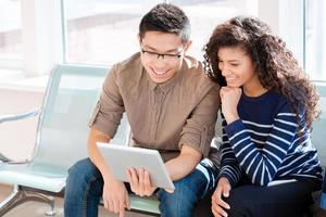 Asian boy and african american girl are using tablet computer photo