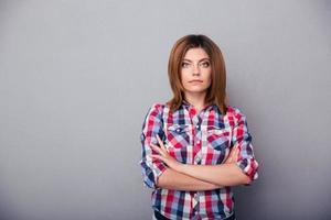 mujer joven de pie con los brazos cruzados