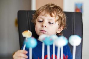 Little blond boy eating colorful cake pops. photo