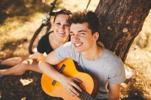 Teenage loving couple with guitar outdoors