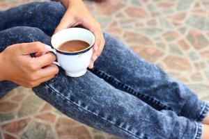 mulher segurando uma xícara de café.