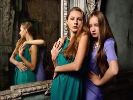 duas lindas mulheres posando em interior obsoleto.