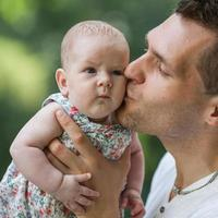 dad and newborn daughter playing in the park in love photo