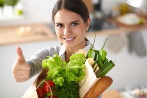 Young woman holding grocery shopping bag with vegetables and showing