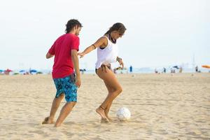 Young couple playing football on the beach at sunset photo