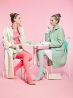 Two girls blonde hair fifties fashion style drinking tea. photo