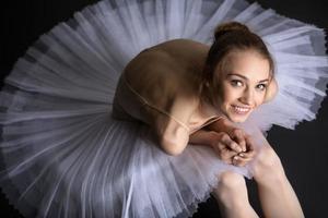 Graceful ballerina sitting on the floor