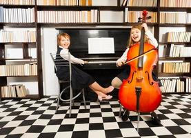 Girls playing on violoncello and the piano photo