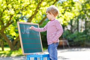 niño pequeño en la pizarra aprendiendo a escribir foto