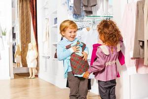 Smiling boy fitting vest and girl holding sweater