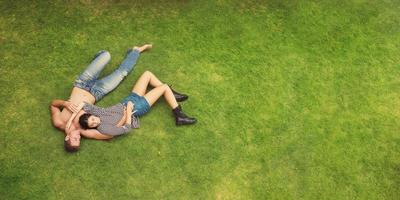 Love young beautiful fashion couple  lying on green grass background