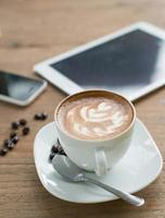 cup of coffee on table in cafe with tablet photo
