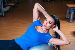 Young happy woman doing fitness exercises with fit ball at