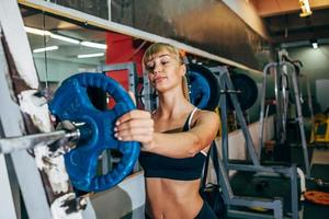 athletic girl sets weight on barbell in the gym