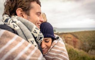 Pareja joven riendo al aire libre bajo una manta en un día frío