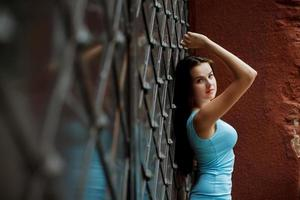 Beautiful young girl standing near fence.