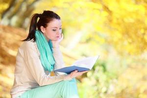 joven relajante en el parque otoñal libro de lectura foto