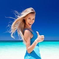 Happy blond girl on beach, showing okey sign. photo