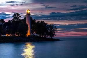 faro que brilla en la puesta del sol foto