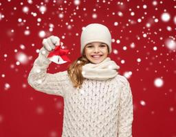 girl in hat, muffler and gloves with jingle bells photo
