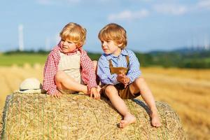 Two little sibling boys and friends sitting on hay stack photo