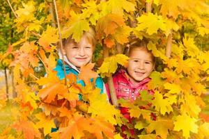 Girl and boy hiding in yellow autumn leaves photo