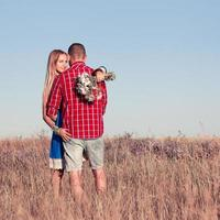 Love story. Beautiful young couple walking in meadow, outdoor