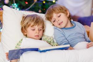 Dos pequeños hermanos rubios leyendo un libro en Navidad