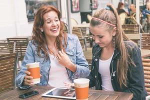 meisjes met behulp van digitale tablet in café