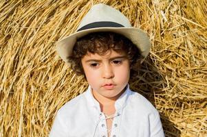 menino de chapéu em pé no rolo de feno