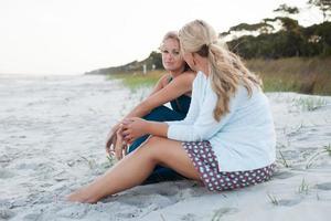 twee vrouwen zitten praten op het strand