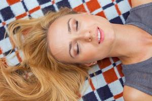 Sensual blonde woman lying in park on blanket. Outdoor photo.