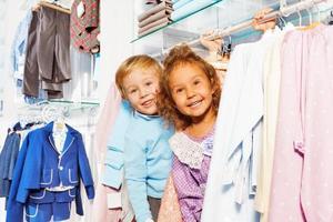 Niño y niña asombrados juegan a las escondidas en la tienda foto