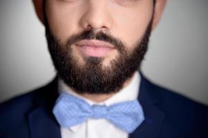 Cerca de hombre guapo con barba y pajarita foto