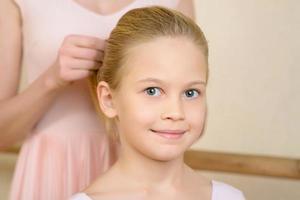 profesora de ballet arreglando peinado de chicas foto