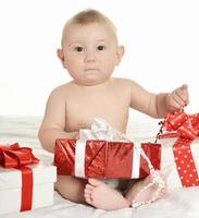 Adorable baby boy with gifts photo