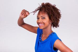 joven mujer afroamericana sosteniendo su cabello afro muy rizado