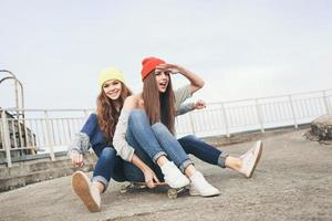 Two young  longboarding girl friends