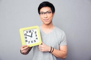 gelukkig Aziatische man met grote klok