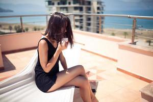 Atractiva mujer joven sentada en la terraza en la hamaca tomando café foto