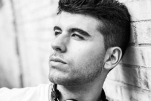 joven guapo con ojos azules posando cerca de una pared foto