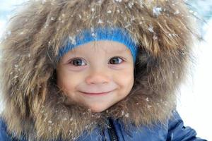 Smiling little boy portrait close-up in the snow photo